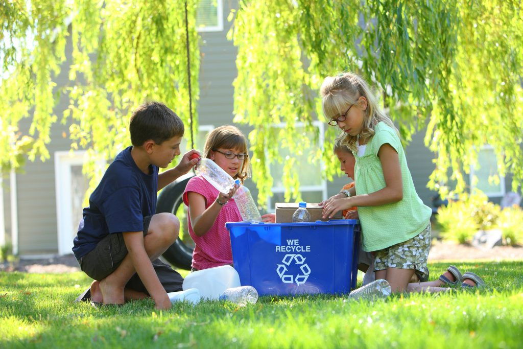 Kids recycling plastic bottles outdoors